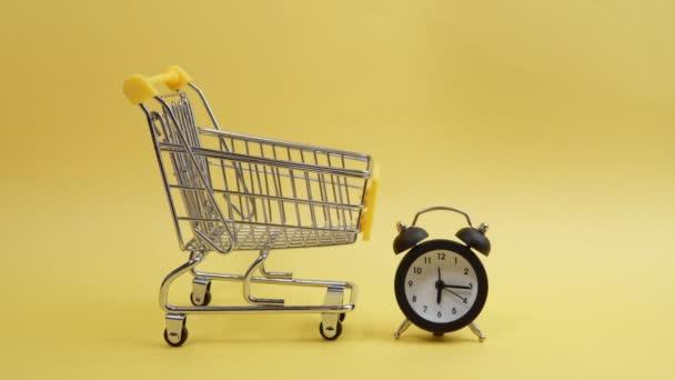 nákupní košík, koncept nákupního času na žlutém pozadí