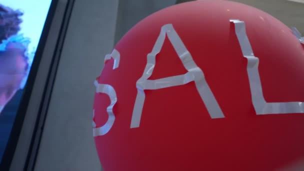 Nápis prodej na červený míč v nákupním centru v obchodě