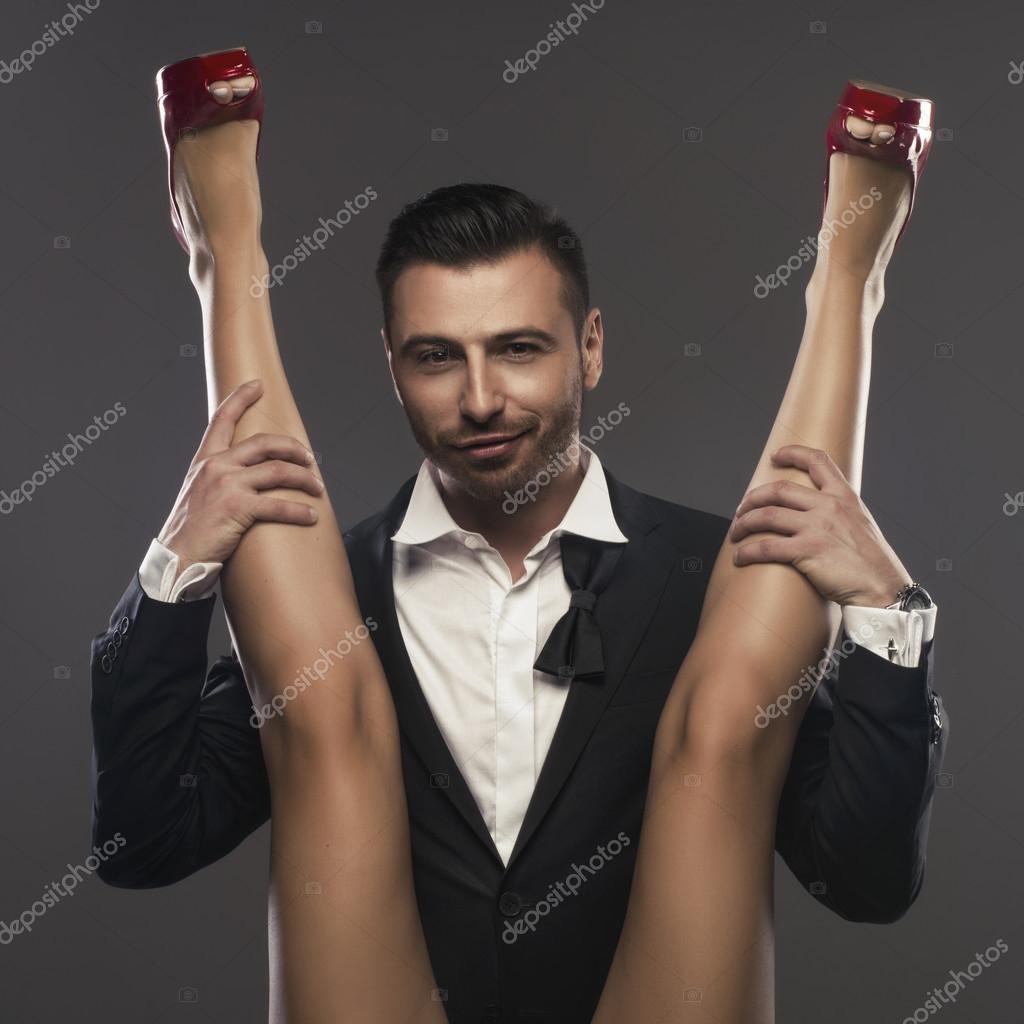 elegenat hombre sentado y se est extendiendo a las piernas de la mujer foto de stock. Black Bedroom Furniture Sets. Home Design Ideas