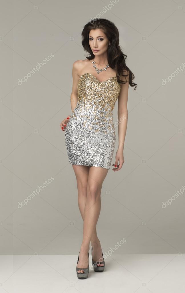 Junge Brünette Dame in Gold - silberne Kleid posiert auf grauen ...