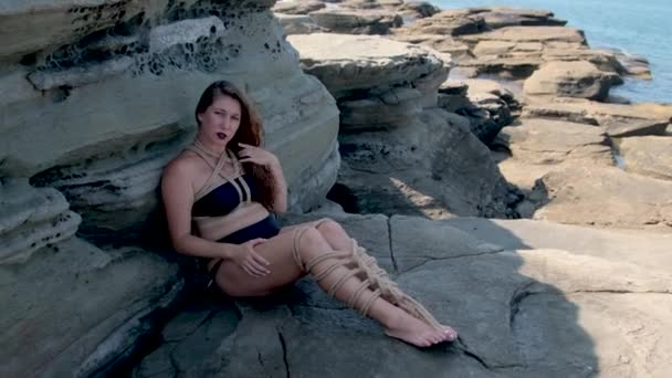 dívka svázaná provazy plave ve vodě a stojí na kamenech. slunečný den, malé vlny