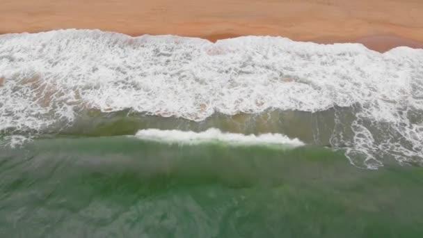 Légi drón lövés kilátás nyílik az óceán hullámai, gyönyörű hullámok nem ér véget keretek egyenként, míg a türkiz tengeri hullámok törnek a homokos parton. 4K