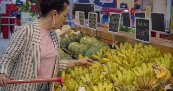 Eine junge Frau in der Lebensmittelabteilung eines Supermarktes kauft Lebensmittel ein, wo die Leute Lebensmittel kaufen. Hübsche Frau kauft Lebensmittel, Obst, Äpfel, Orangen auf dem Markt, im Supermarkt.