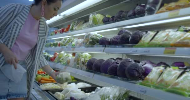 Mladá žena v nákupním oddělení supermarketu kupuje jídlo, koncepci, kde lidé kupují jídlo. Hezká žena kupuje jídlo, ovoce, jablka, pomeranče na trhu, v supermarketu.