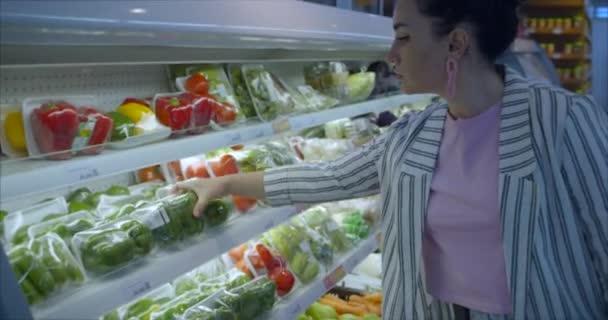 Hübsche Frau kauft Lebensmittel, Obst, Äpfel, Orangen auf dem Markt, im Supermarkt.