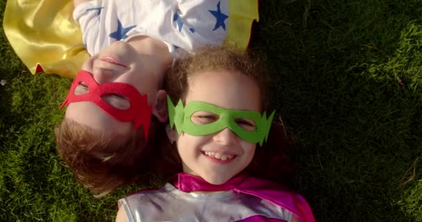 Portrait of two children superheroes, little girl and a baby boy lie on the grass in superhero costumes. Funny kids in a raincoat and mask playing superheroes look at the camera, smile, rejoice.