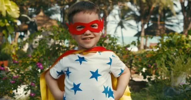 Aranyos Boldog Fiú A Szuperhős Jelmezben, A Kölyök Szuperhőst játszik, A Gyermek Vörös És Sárga köpenyben És A Hős Maszkja. Szuperhős és hatalom koncepció. Portré közelről.