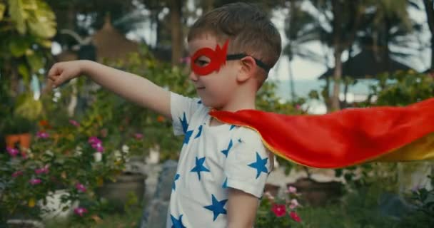 Aranyos kisfiú egy szuperhős jelmezben, piros köpenyben és hősmaszkban, integetve a távolba nézve, a kölyök egy szuperhőst játszik a szabadban, a gyerek erőt mutat. Szuperhős és hatalom