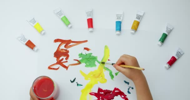 Close-up footage top view of how a little boy draws with a brush on a white sheet of different colors with paints, draws abstractly makes strokes with an artistic brush using watercolors.