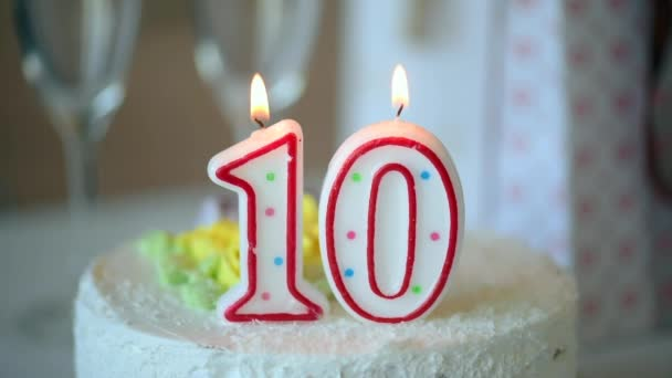 Születésnapi gyertya, mint a 10-es számú 10-es számú az asztalon lévő édes torta tetején, 10. születésnap