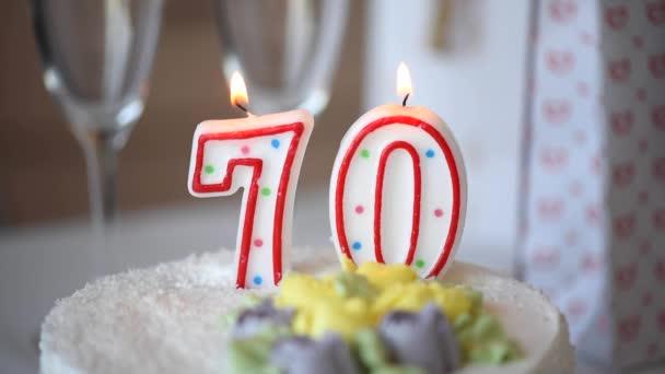 Geburtstagskerze als Nummer siebzig 70 auf süßem Kuchen auf dem Tisch, 70. Geburtstag