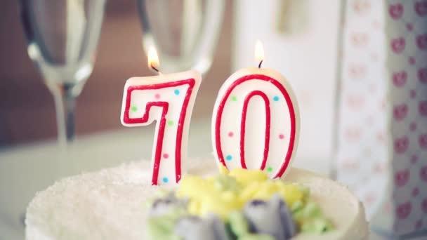 Geburtstagskerze als Nummer siebzig 70 auf süßem Kuchen auf dem Tisch, 70. Geburtstag, getöntes Video HD