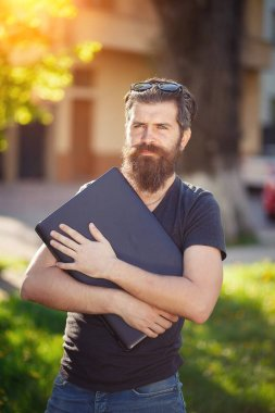 Cheerful bearded male developer with a long beard and dark gray hair in a shirt and jeans hugs a laptop on the background of a green park in spring