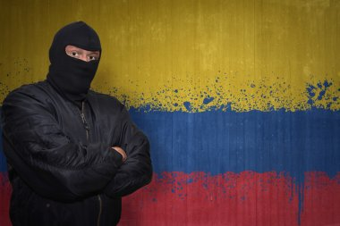 dangerous man in a mask standing near a wall with painted national flag of colombia