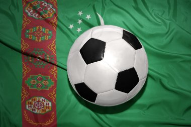 black and white football ball on the national flag of turkmenistan
