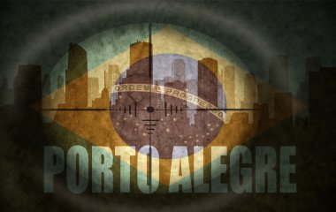 sniper scope aimed at the abstract silhouette of the city with text Porto Alegre at the vintage brazilian flag