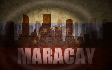 sniper scope aimed at the abstract silhouette of the city with text Maracay at the vintage venezuelan flag. concept