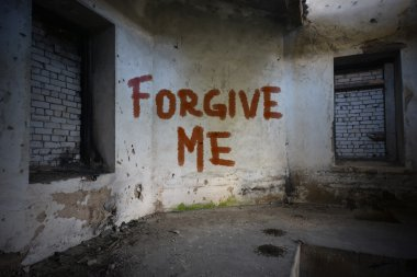 text forgive me on the dirty old wall in an abandoned ruined house
