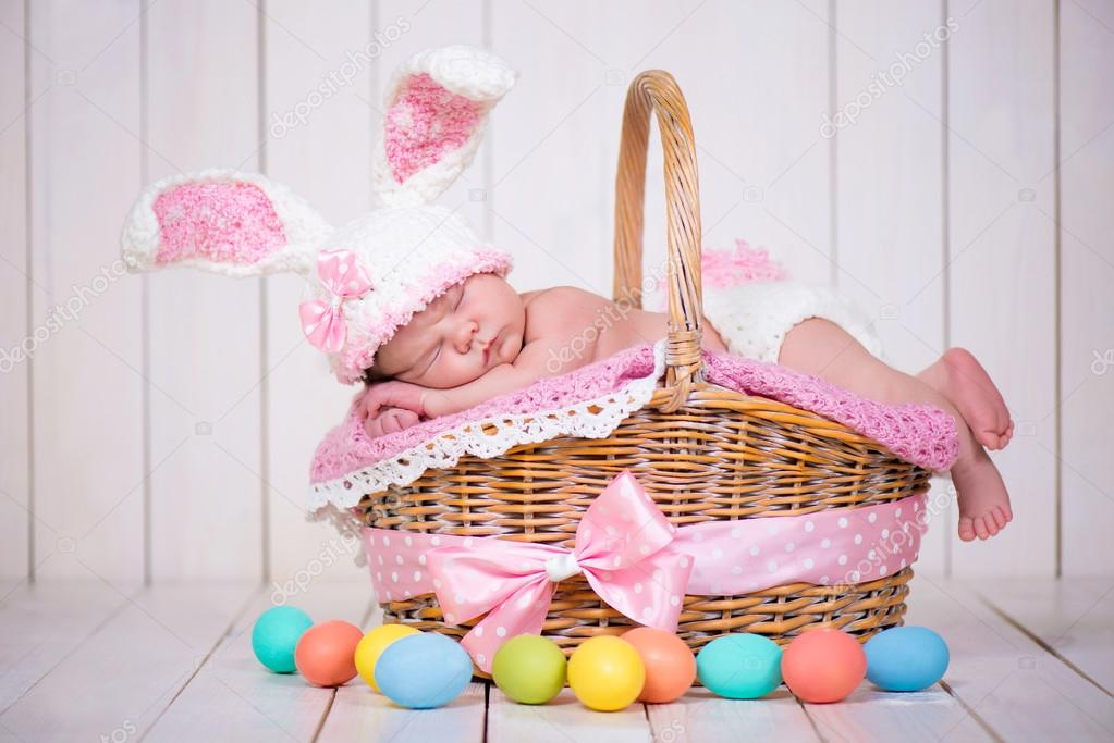 Newborn baby girl in a rabbit costume has sweet dreams on the wicker basket. Easter Holiday