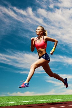 Sport running girl on the background of stadium and sky