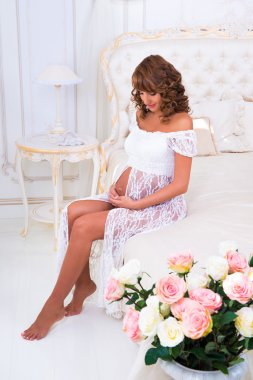 Happy pregnant girl in a white lace dress sitting on a bed near roses