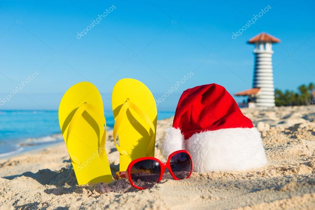 New Year celebration at the seaside. Santa hat, sandals, sunglasses - christmas holiday at sea.