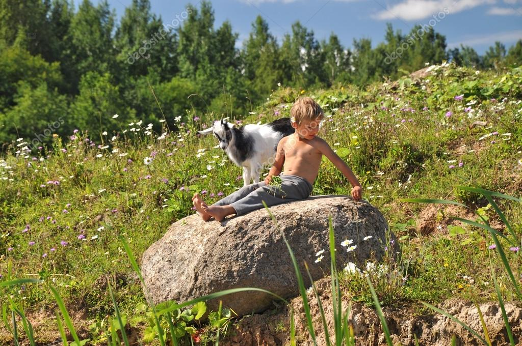 Boy and goat playing on a stone