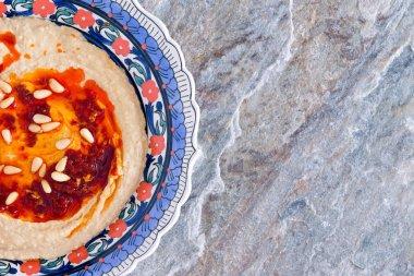 Bowl of hummus on a natural stone countertop