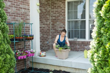 Woman tending to newly potted plants on her patio