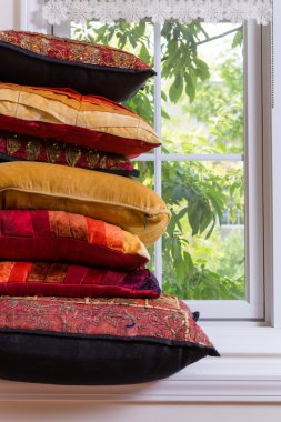 Piled Authentic Pillows In Front Glass Window