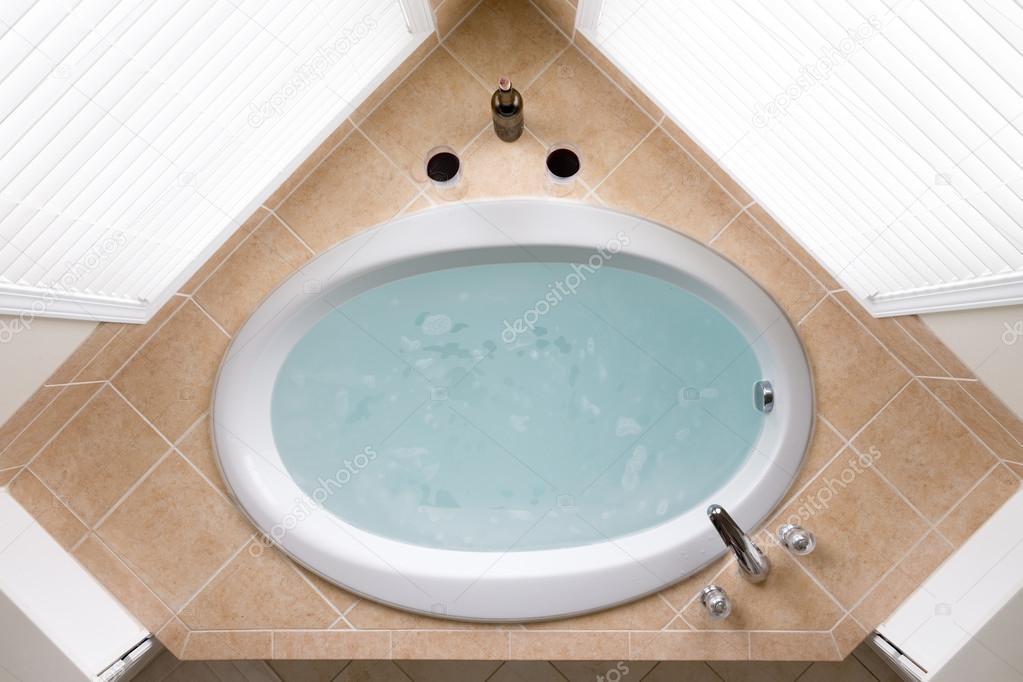 Stylish corner oval bathtub in a tile surround