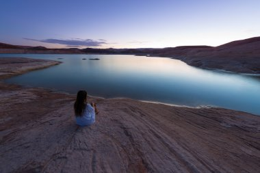 Single Woman sitting by the lake