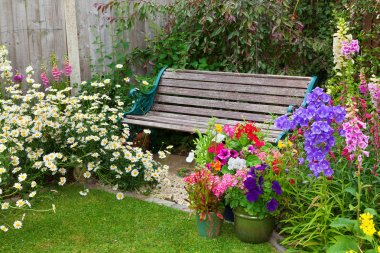 Cottage garden with bench and containers full of flowers