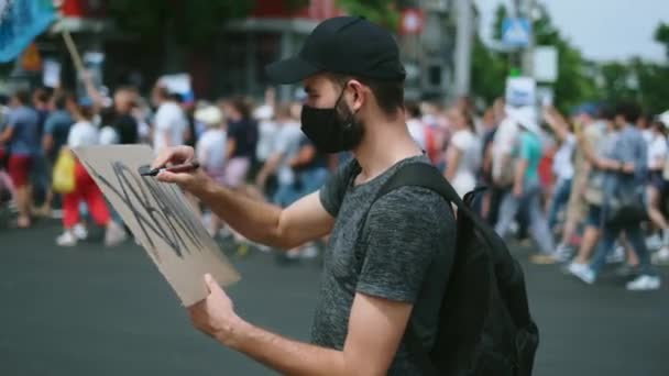 Masked riot activist man drawing poster sign, poster banner. Rebel on rally.