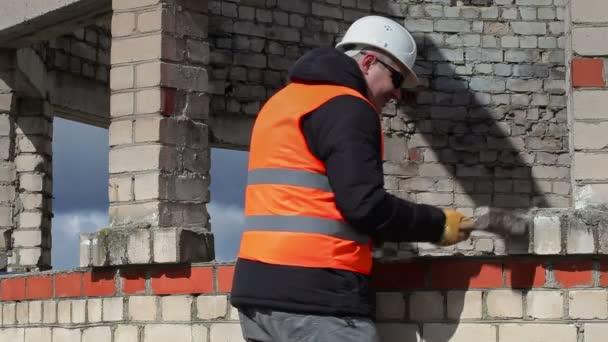 Dělník s kladivem u cihlové zdi