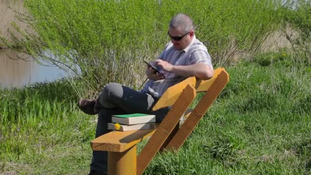 Man with tablet PC and books on bench near river