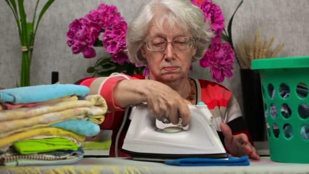 Stará žena, žehlení a ručníky