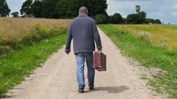 Muž s kufrem odchází na venkovské silnici