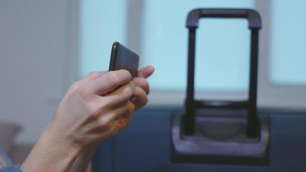 Žena pomocí chytrého telefonu v blízkosti kufru zblízka