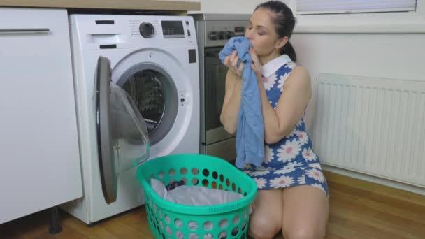 Frau riecht gereinigte Kleidung in der Nähe der Waschmaschine
