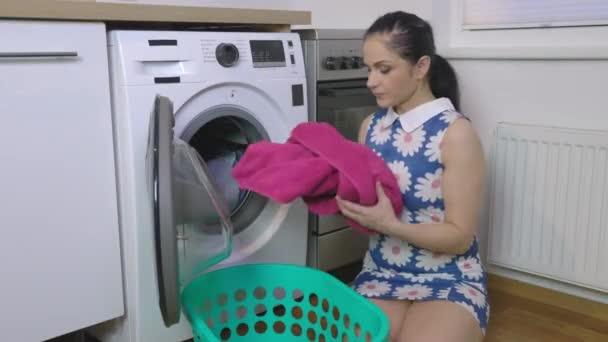 Lächelnde Frau zeigt Daumen hoch neben Waschmaschine
