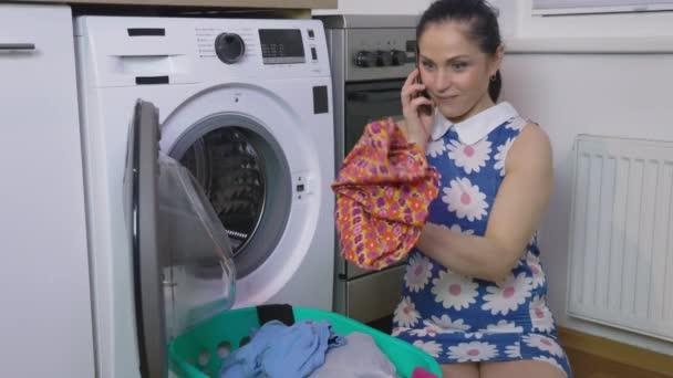 Überraschte Frau hält Mann Unterwäsche in der Nähe der Waschmaschine