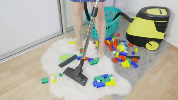Žena s vysavačem čistící koberec v chaotické místnosti