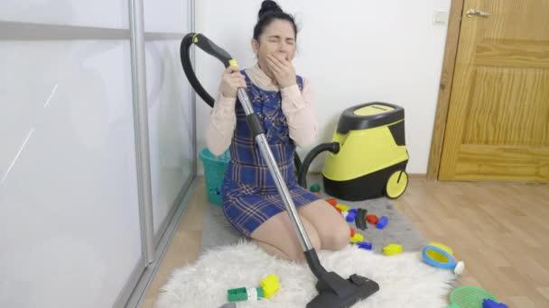 Müde Frau gähnt und benutzt Staubsauger