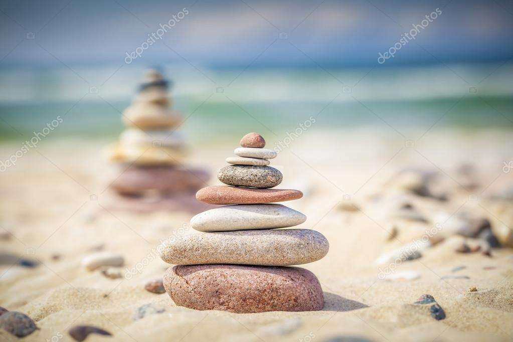 Balanced stones stacked in pile on a sand near sea