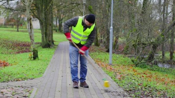 Pracovník zametá listí v parku