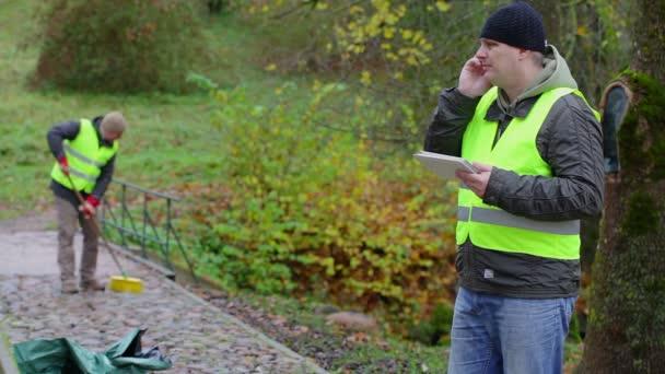 Foreman na mobil u pracovníka, který sbírá listy