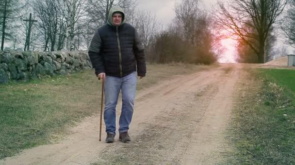 Muž s vycházkovou holí na venkovské silnici