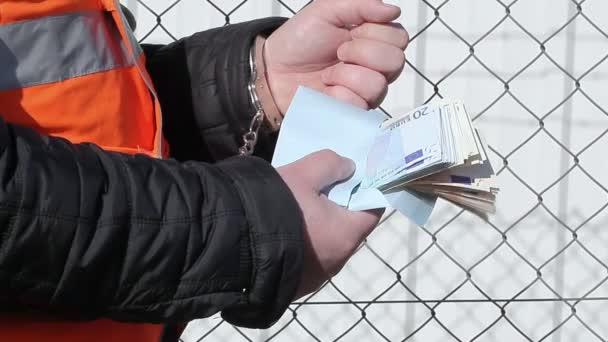 Man in handcuffs with money