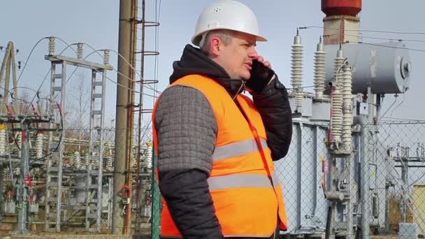 Dělník mluví do mobilu v elektrárně